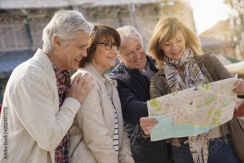 Group of senior tourists reading city map
