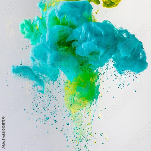 projekt-z-plynaca-turkusowa-niebieska-i-zielona-farba-w-wodzie-z-kroplami-na-szaro