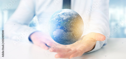 Fototapeta Businessman holding a 3d rendering particles earth globe