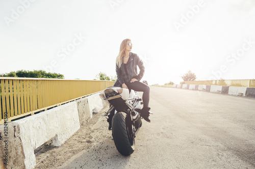 Beautiful woman biker posing sitting on a motorbike