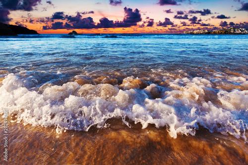 Detalle de la orilla del mar y arena. Paisaje marino y olas rompiendo en la costa.Puesta de sol en la playa