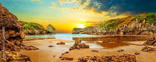 Fotobehang Oranje Impresionante e idilico paisaje de playa y mar en Cantabria.Acantilados y montañas.Puesta de sol y naturaleza salvaje