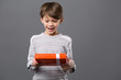 Unexpected surprise. Joyful excited boy standing against grey background while receiving a present
