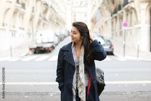 Chinese girl standing in street background, walking after classes. Concept of international students and strolling in city.
