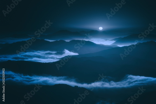 dark landscape with foggy mountains and full moon at night