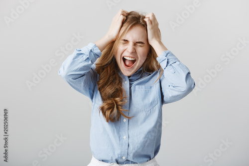 Cannot handle pressure anymore. Tensed fed up european female model in blue-collar shirt, yelling or screaming while holding hands on head with closed eyes, feeling pain or suffering depression