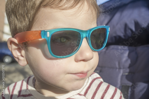 Blue eyes toddler boy protected with sunglasses. Children eye health concept