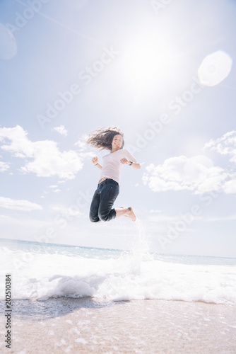 A girl jumps on the sand of the beach