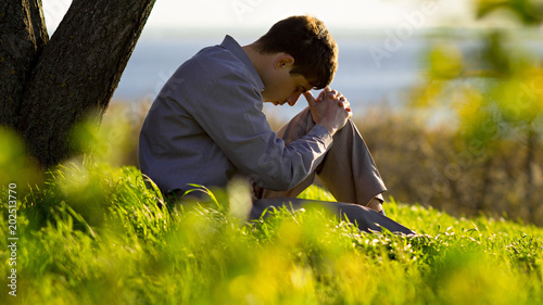 young man praying to God in the nature bowing his head to his knees, concept religion