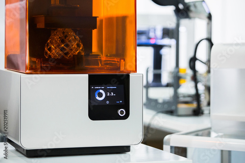 A stereolithography 3d printer in the laboratory prints a structure from a photopolymer.  On the display the process indicator and the number of layers. Creating scaled model by UV polymerization.