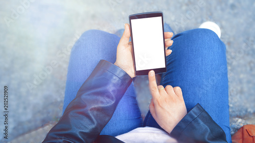 Young girl wearin jeans and leather jacket using a mobile and taking coffee. Empty copy space for Editor's content.