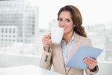 Beautiful content businesswoman using tablet drinking coffee - 202544793