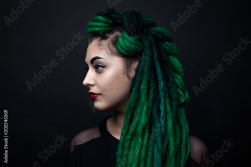Portrait of a pretty girl with long green dreadlocks. © dinachi