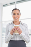 Smiling businesswoman holding a coffee - 202550512