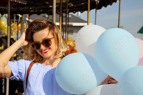 Plexiglas Amusementspark Beautiful young woman with balloons in the amusement park