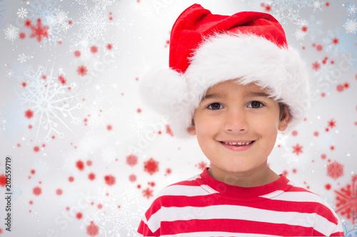 Fototapeta Cute little boy in santa hat against snowflake pattern