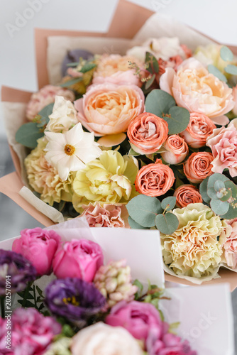 two bouquet of beautiful flowers on gray table. Floristry concept. Spring colors. the work of the florist at a flower shop. Vertical photo