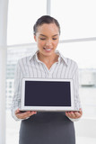 Smiling businesswoman showing laptop screen and looking at it - 202582183