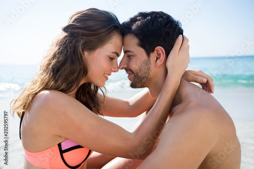 Side view of young couple sitting face to face at beach