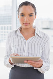 Serious businesswoman using her tablet pc - 202604131