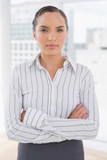 Serious businesswoman standing in an office crossing arms - 202605360