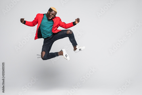 Full length portrait of a cheerful afro american man jumping isolated on a white background © F8studio