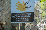 Warning sign on electrified wire fence in a zoo