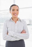 Smiling businesswoman standing in office - 202626316