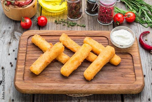 Fototapeta Crunchy Breaded mozzarella cheese sticks with mustard sauce. Beautiful stylish menu.