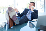 Businessman relaxing in a swivel chair and having a phone call - 202635524