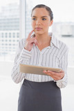 Pensive businesswoman holding a tablet pc - 202646599
