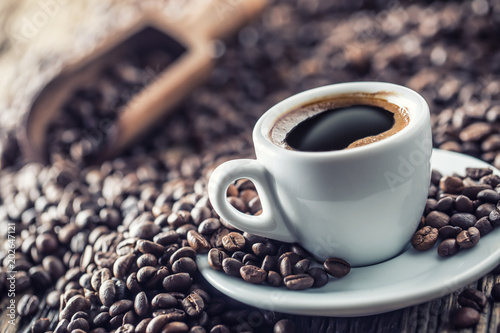 Cup of black coffee with beans on wooden table - 202647121
