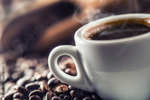 Cup of black coffee with beans on wooden table