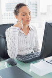 Pretty thoughtful businesswoman sitting at her desk - 202668781