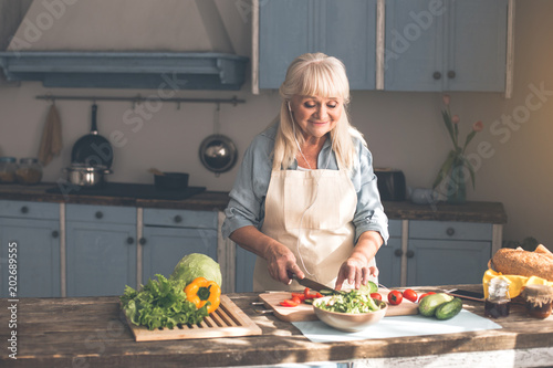 Enjoying household. Cheerful old woman is chopping cucumber and tomato for salad. She is listening to music from earphones and smiling - 202689555