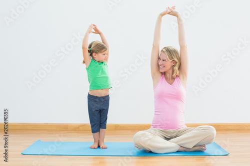 Ciężarna uśmiechnięta matka i córka robi joga wpólnie