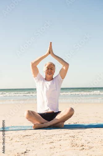 Senior man sitting on mat while meditating at beach
