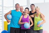 Cheerful people with medicine balls in fitness studio