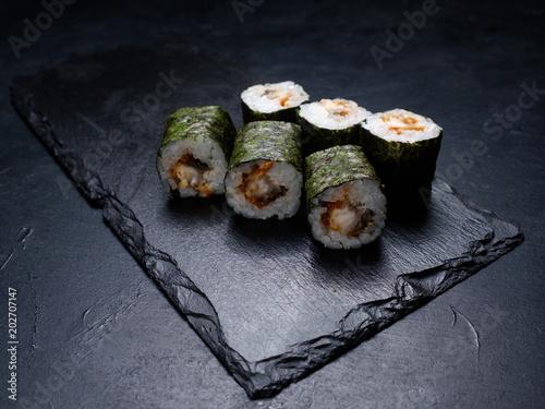 Plexiglas Sushi bar sushi rolls with salmon covered in nori on dark background. Japanese traditional food preparing craft