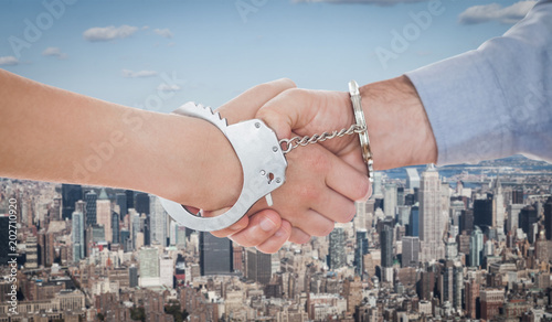 Foto Murales Handcuffed business people shaking hands against new york