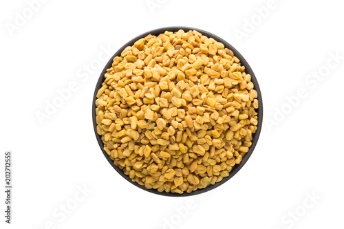 fenugreek seed in clay bowl isolated on white background. Seasoning or spice top view