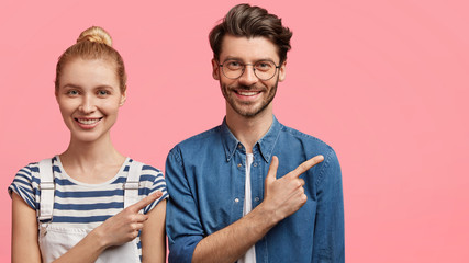 Positive European friends dressed in fashionable clothes, stand next to each other, point aside at blank copy space for your advertising content. Pretty blonde woman with hair bun and hipster guy © Wayhome Studio