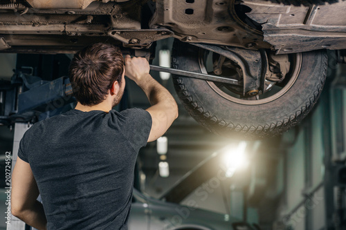 Wall mural Auto mechanic working at auto repair shop under car with tool