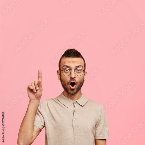Indoor shot of surprised bearded attractive male with amazed expression, keeps mouth widely opened, indicates with fore finger upwards, attracts your attention at blank copy space on pink background © Wayhome Studio