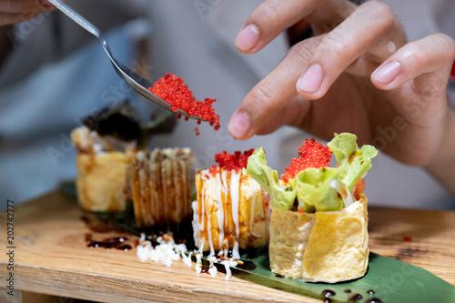 Fotobehang Sushi bar Closeup of chef hands preparing japanese food.