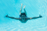 Young man swimming underwater - 202769703