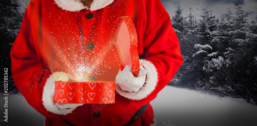 Fotobehang Rood traf. Santa claus opening a gift box against snow scene