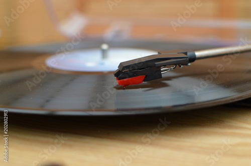 Closeup of tonearm and stylus on a wooden vinyl record player