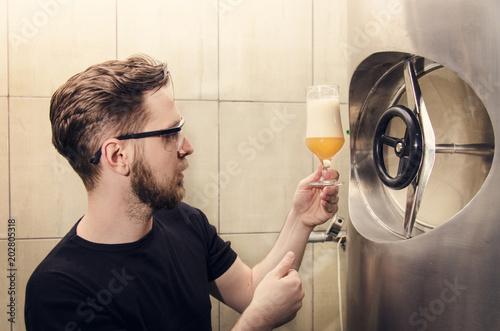 Fototapeta Beer brewer, looking and tasting beer, quality control