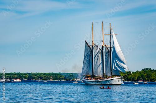 Single Tall Ship sailing among other boats
